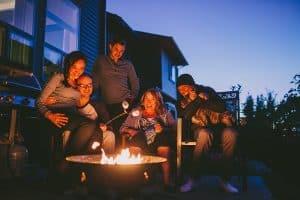 family roasting marshmallows around propane fire pit
