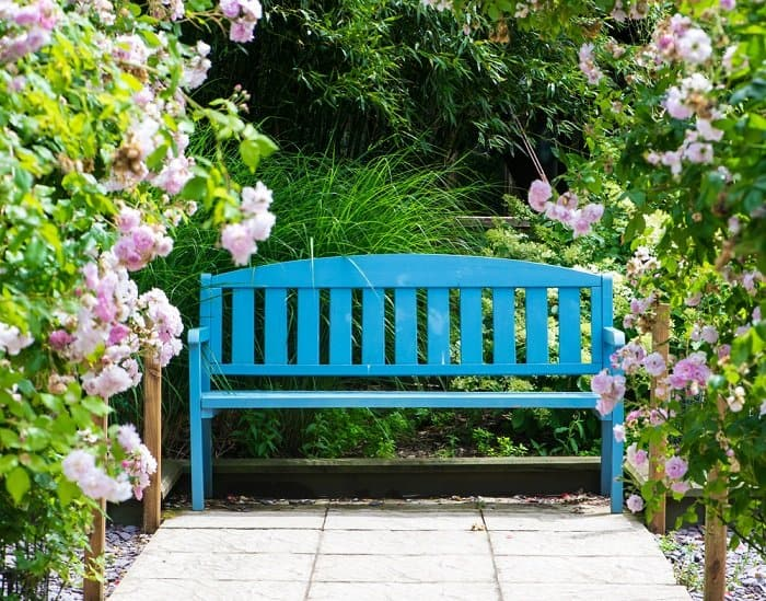 a blue bench on a patio surrounded by flowers and other plants