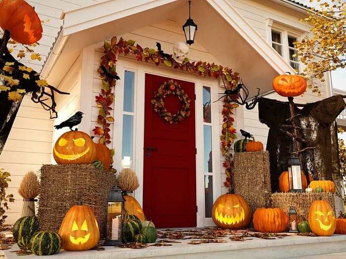 a front porch decorated for halloween, including jack-o-lanterns, reefs, and hay