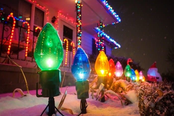 multicolored lights on a sidewalk covered in snow outside of a house. Roof line with lights across it, as well as candy cane lights hanging on rails.